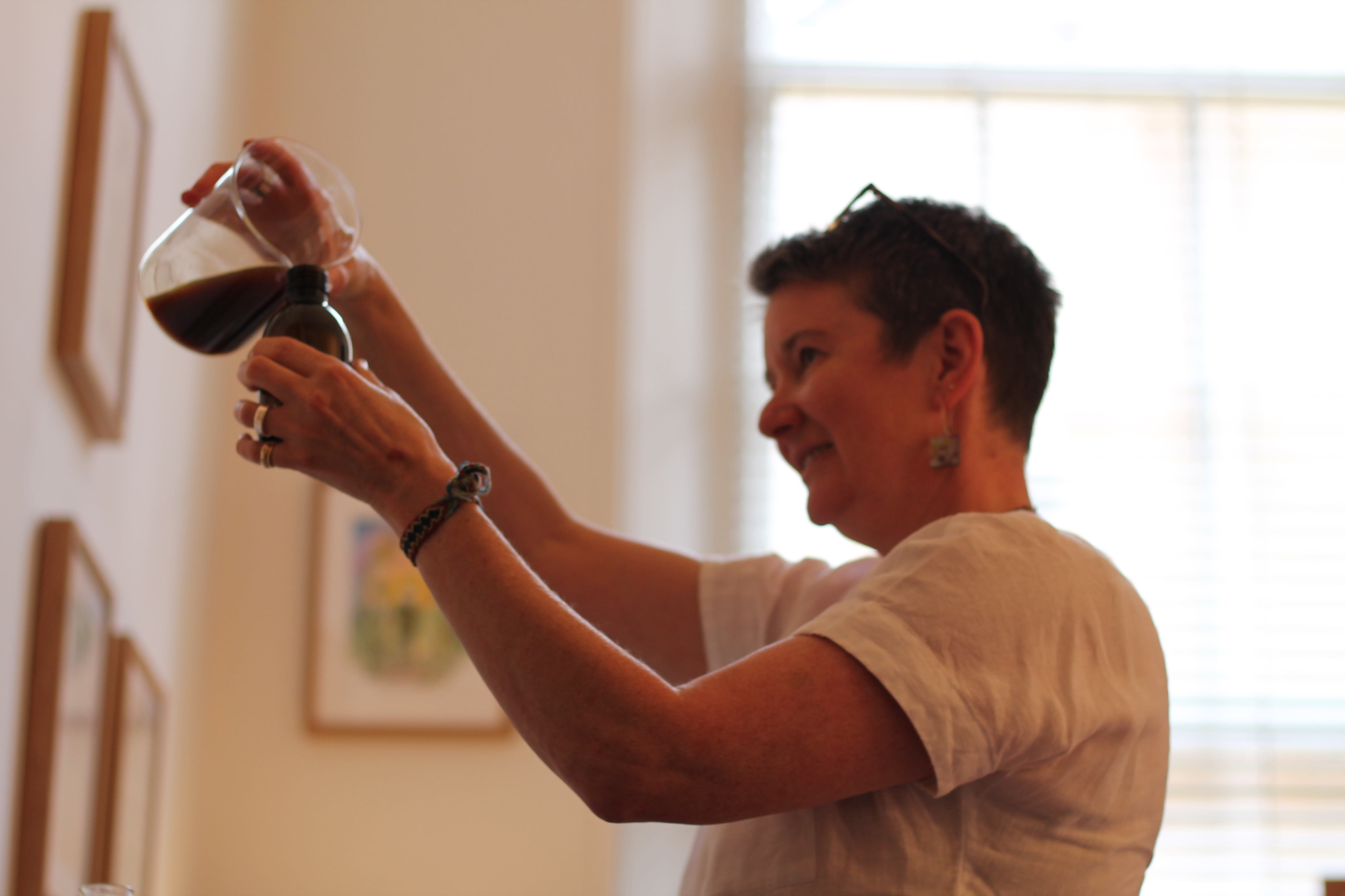 A photo of a lady pouring liquid into a bottle.