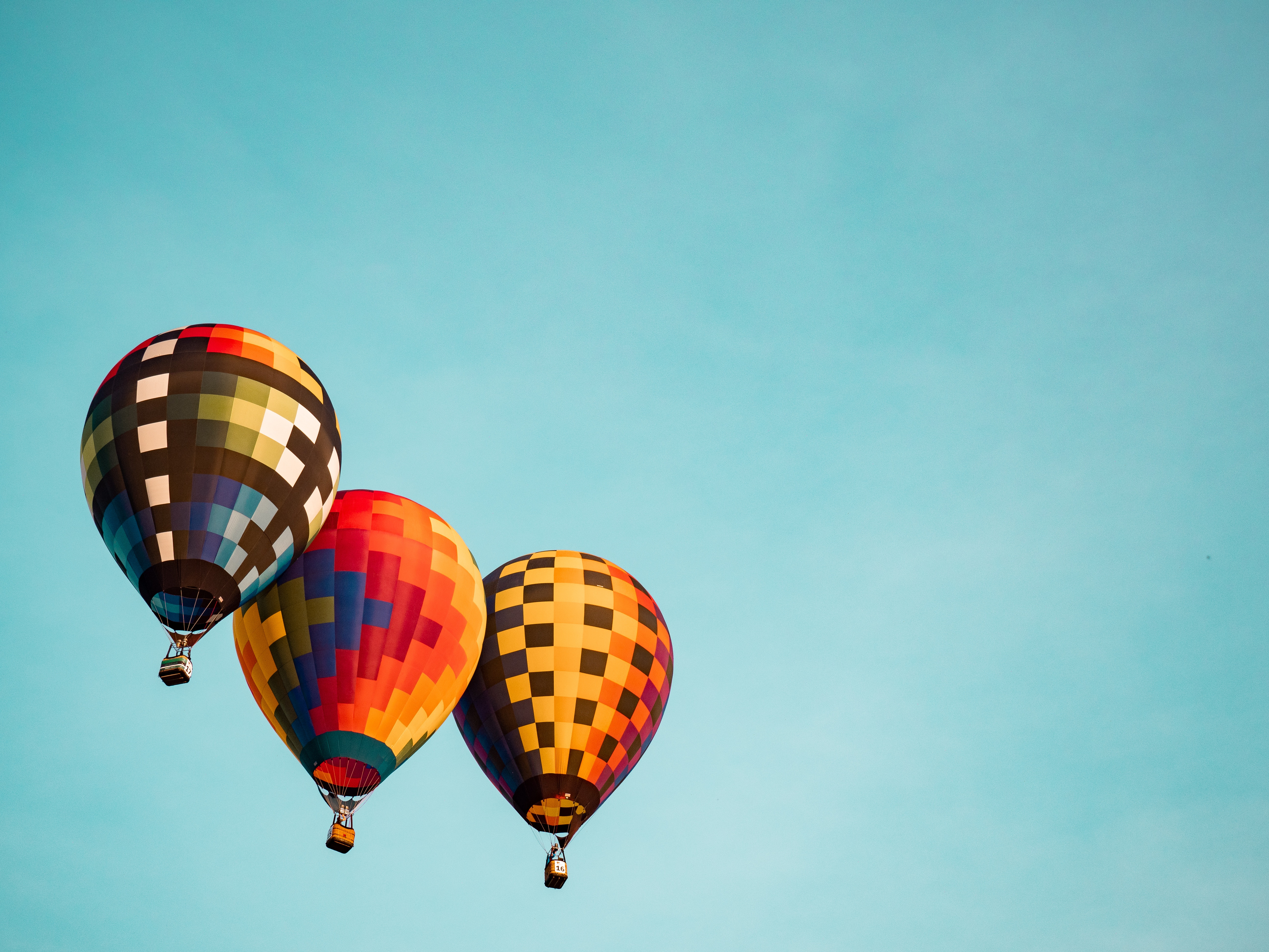 3 brightly coloured hot air balloons against a bright blue sky