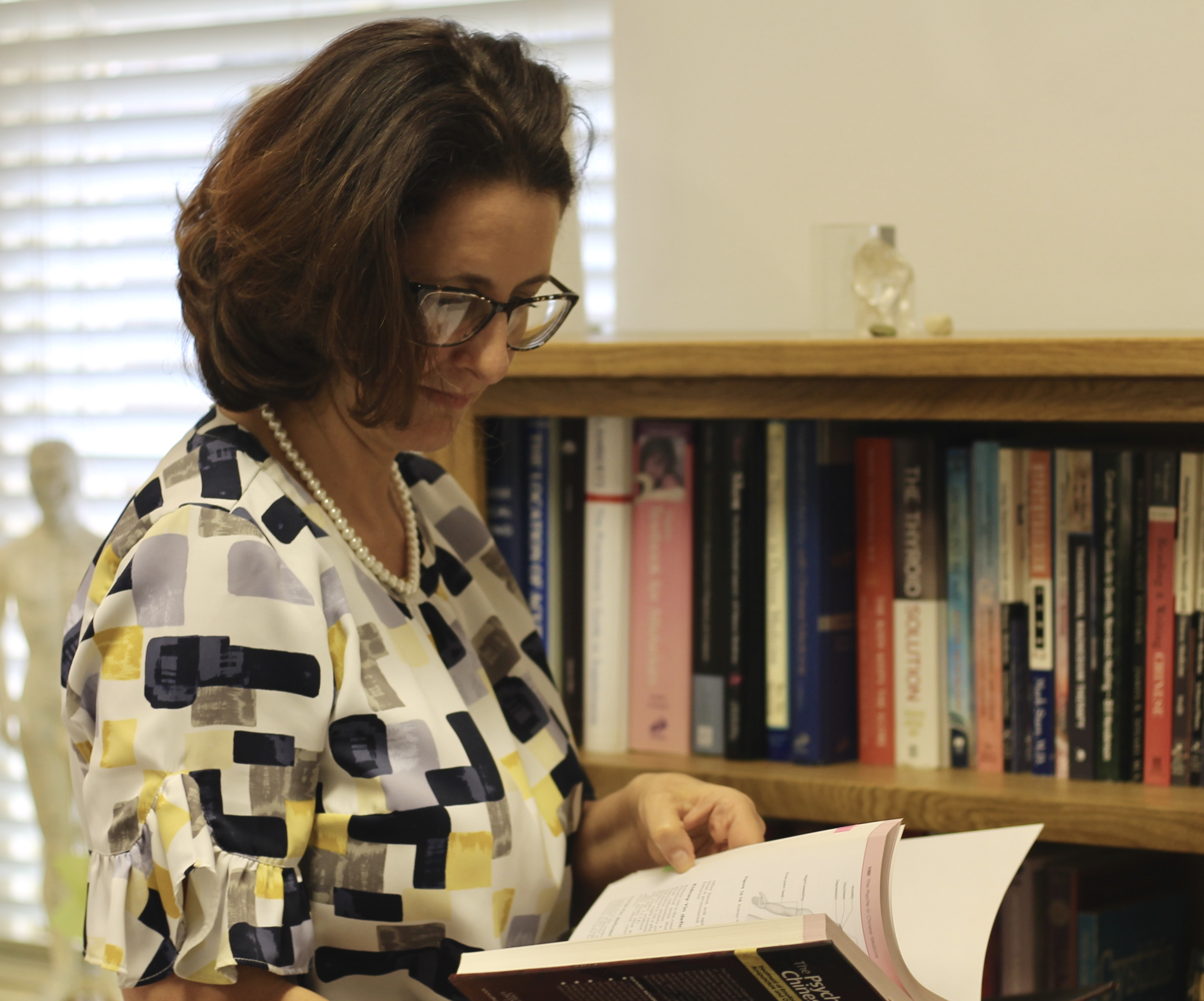 A photo of a lady standing by a bookshelf reading a book