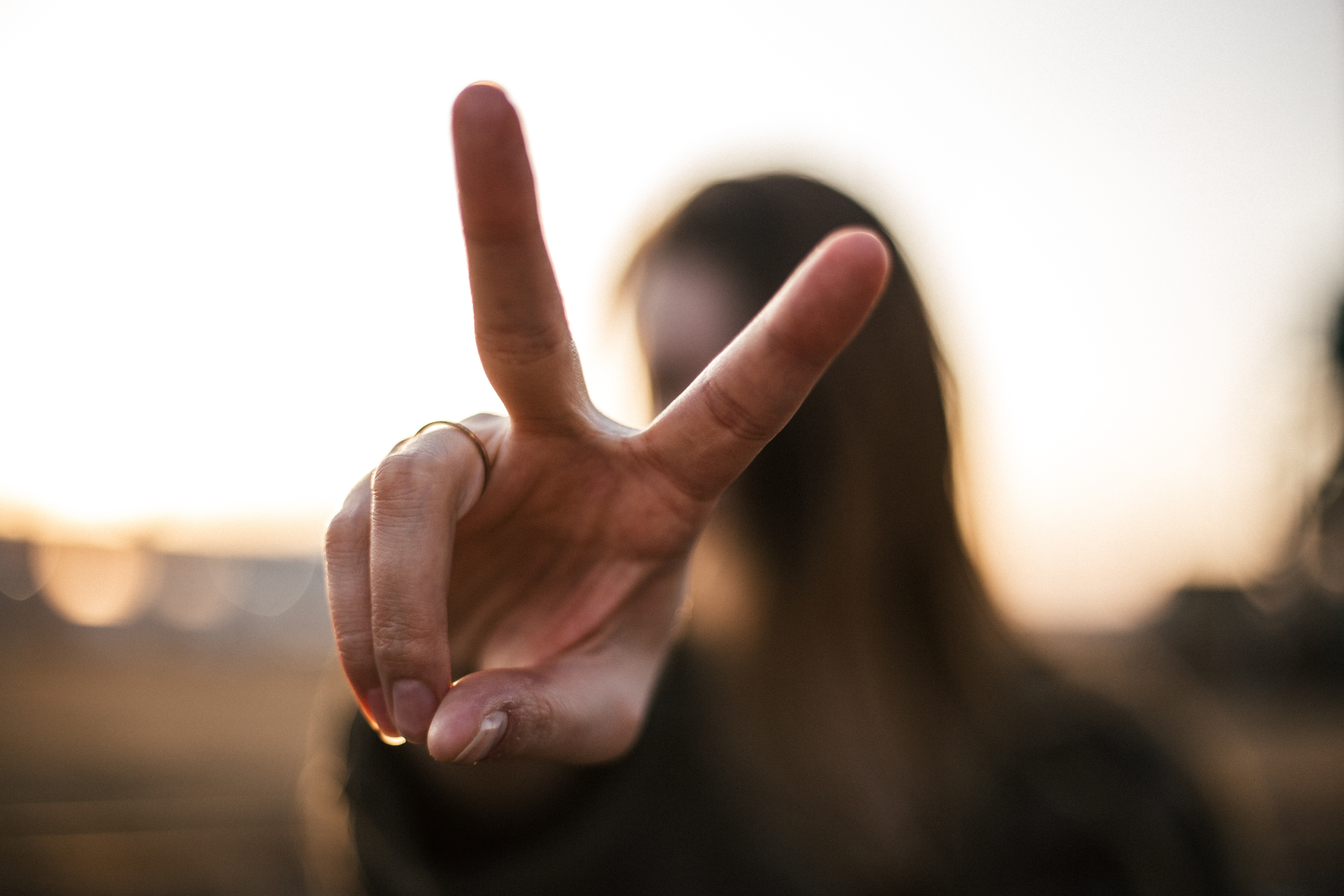 A figure holding up two fingers in a peace sign.